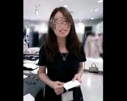 ネイビーワンピを纏うショップ店員の色鮮やかな空色サテンPを逆さ撮りの画像