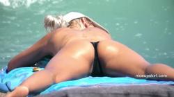 ビーチでうつ伏せ股を開いて肌を焼いてるトップレス熟女のキワドイ股間を隠し撮りwww【海外盗撮】の画像