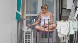 【パンチラ】ベランダでタバコを吸ってるノーブラ美女のパンチラを隣のアパートから隠し撮りwww【海外盗撮】の画像