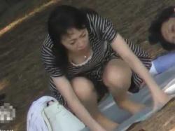 公園パンチラ胸チラ!しゃがんだり横になったりして谷間も生理パンツも丸見えの女性の画像