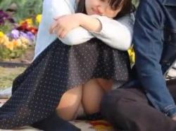 公園座りパンチラ!彼氏に寄り添い幸せそうな顔して純白パンツ丸見えのむっちり彼女の画像