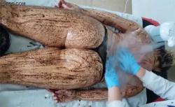 【マッサージ施術動画】泥パックを背面に塗られる女性の様子の画像