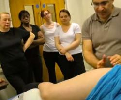【マッサージ講習会動画】真剣な表情で下半身マッサージをされる女性を見つめる受講者達の画像