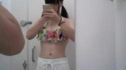 【盗撮・試着室】ツインテールの可愛らしい女子高生が洋服屋の試着室でビキニの下に履くショートパンツを試着してる様子を盗撮の画像