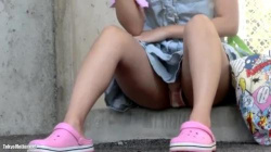 縁石に座ってスマホをいじってる水色ワンピの美少女のピンクのパンティが丸見えだったのでこっそり盗撮の画像
