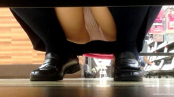 【eros1166しゃがみパンチラ】ピンクPのしゃがみパンチラを長々と撮られる股間の膨らみと白い太ももがエロいメガネJKの画像