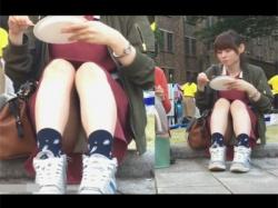 【パンチラ盗撮動画】学園祭真っ最中の大学のキャンパスで地面に座りパンチラしていることに気付かず出店の食べ物に夢中な女子大生!の画像