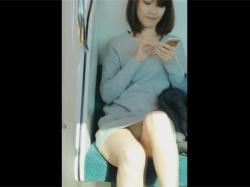 【対面パンチラ盗撮動画】電車内で対面に座ったミニのニットワンピのお姉さんがスマホに夢中で一瞬さらけ出す純白パンチラ!の画像